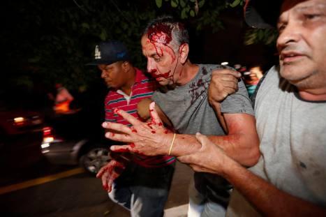 SAO05. SAO PAULO (BRASIL), 05/04/2018.- Un manifestante opositor (c) del expresidente brasileño Luiz Inácio Lula da Silva es ayudado por dos hombres tras ser presuntamente agredido por simpatizantes de Lula hoy, jueves 5 de abril de 2018, en Sao Paulo (Brasil). EFE/Sebastião Moreira/ATENCIÓN EDITORES: CONTENIDO GRÁFICO EXPLÍCITO